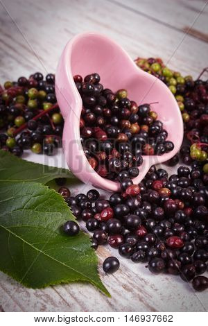 Fresh Elderberry With Leaf In Glass Dish On Old Wooden Background