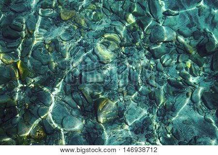 Sparkling with gild pebbles under clear aquamarine water