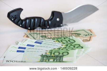 Knife placed on pile of american dollar and euro bills on white background
