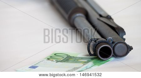 gun and euro banknotes on a white background