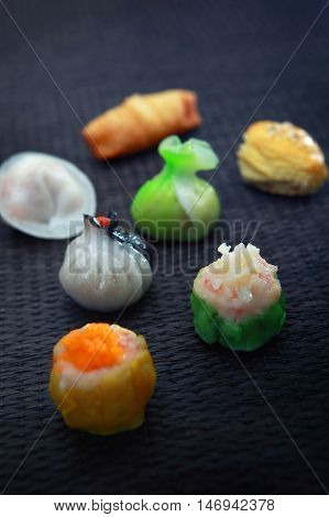 Colorful Chinese Dim Sum on a Black bamboo Mat