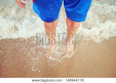 BLURRED IMAGE, FOCUS ON ANKLES AND TOES, long exposure, MOTION BLUR ON WAVES, Boy standing in the waves on the beach