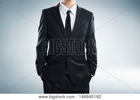 close up part of man body in black suit with hands in pockets on white background; business concept