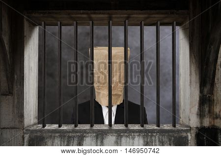 Businessman with brown paper bag on head, in jail