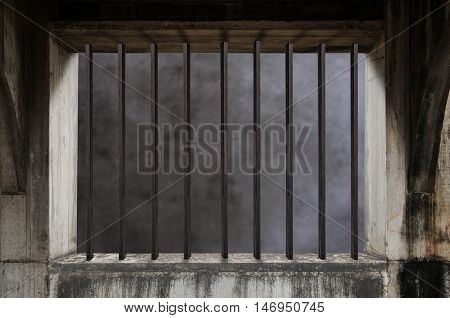 Interior of a prison cell with light shining through a barred window