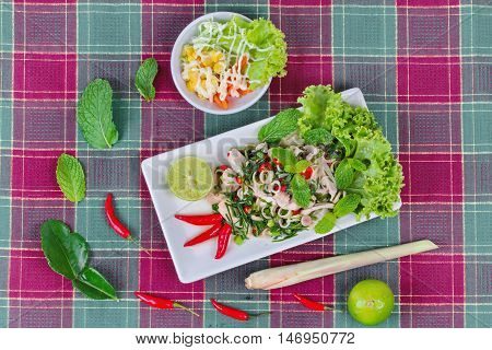Spicy and sour mixed herb salad with pork and chicken  with side dish as mini vegetable salad and streamed gourd  wrap vermicelli and minced pork in bone soup on red green.  Top view.