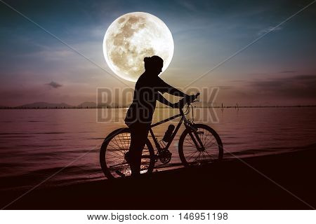 Silhouette of bicyclist in action enjoying the view at seaside on bright full moon sky background. Active outdoors lifestyle for healthy concept. The moon were NOT furnished by NASA.