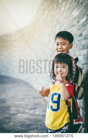Brother holding hand his sister together and smiling happy. Asian pretty girl with thumb up. Tourist child relaxing outdoors at daytime travel on vacation. Vintage effect and cream tone.