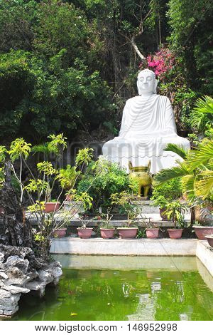 Marble statue of Buddha in garden near to Pagoda on the marble mountain between Hoi An and Da Nang, Vietnam