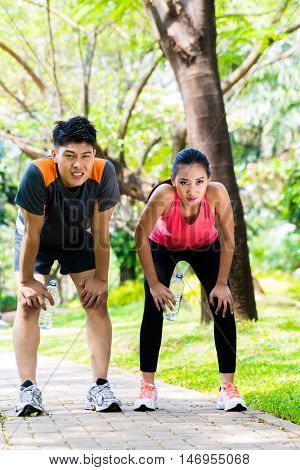 Asian Chinese man and woman are out of breath after jogging in city park for sport fitness