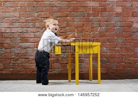 Stylish little gentleman in a bow tie standing near a yellow table on brick wall background