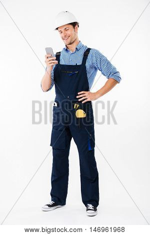 Full length portrait of a handsome male builder standing and using mobile phone isolated on a white background