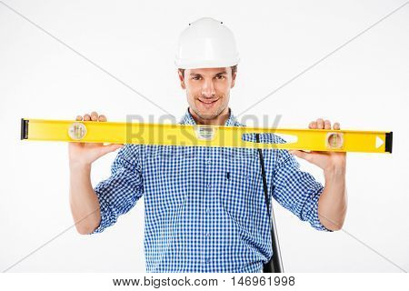 Happy young man builder in building helmet holding spirit level