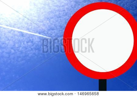 Road sign against the blue sky and clouds .