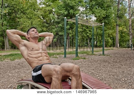 Young Man Doing Crunches On Sit-up Board