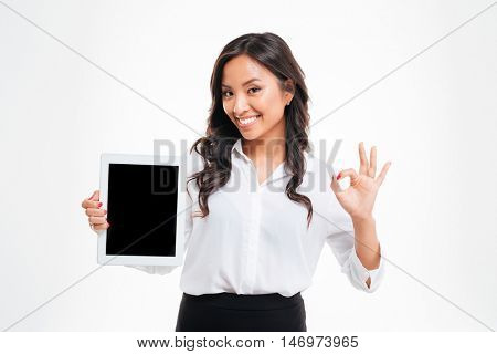 Cheerful young asian businesswoman holding tablet with blank screen and showing okay gesture over white background