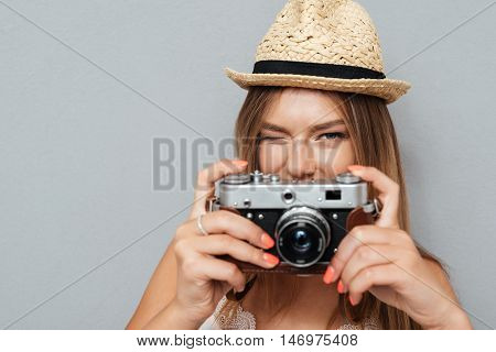 Attractive young girl in hat winking and holding camera isolated on a gray background
