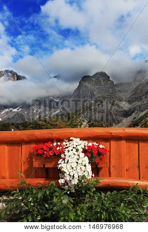 Large tourist center in the majestic Austrian Alps. Fence cozy cafe is decorated with flowers