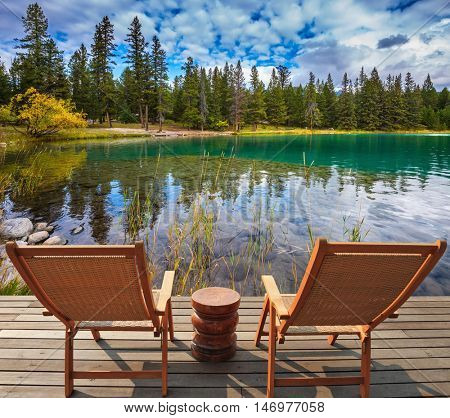 Pretty round lake in the coniferous forest. Two comfortable lounge chairs on wooden pedestal on the lake. Canadian Rocky Mountains, Jasper National Park