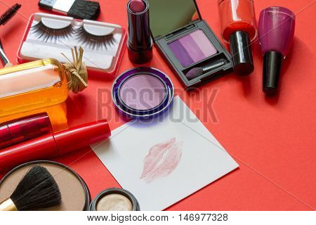 Cosmetics and red lipstick on the paper abstract background concept