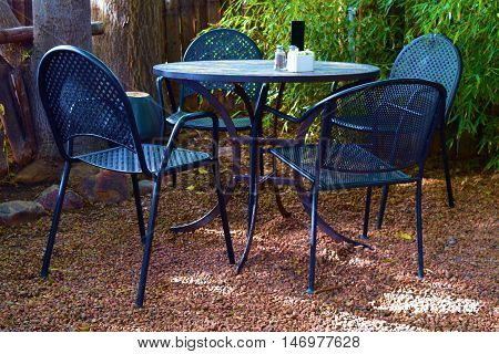 Patio furniture including a table and chairs taken in a courtyard garden