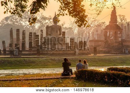 Japanese Man take a photo european traveller in sunrise time at Sukhothai historical park the old town of Thailand in 800 years ago