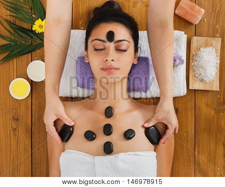 Black marble stone massage in spa. Beautician with female patient in wellness center. Professional cosmetologist make relaxation procedure to beautiful indian girl in beauty parlor, top view on wood