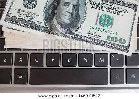 Batch of one hundred dollar bills on keyboard, close-up. American money banknote on laptop. Income through internet, programming concept