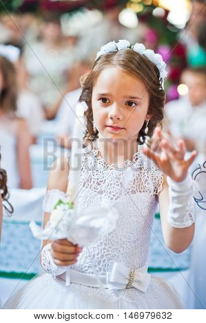 Portrait Of Cute Little Girl On White Dress And Wreath On First Holy Communion With Burning Candle A