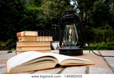 kerosene lamp and old books on the table in the garden