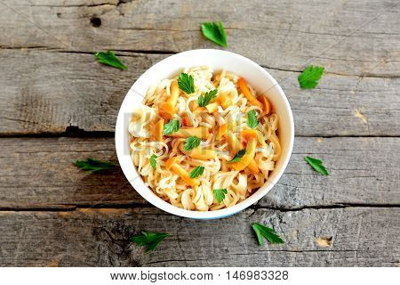 Pasta with mushrooms and herbs recipe. Pasta with marinated chanterelles mushrooms in a bowl isolated on old wooden background. Vegetarian recipe. Closeup