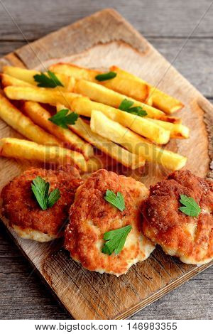 Turkey breast cutlets served with fries on cutting board and on an old wooden background. Cutlets prepared from minced turkey meat and fried in vegetable oil in a frying pan. Closeup. Top view