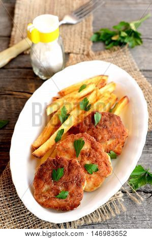 Fried meat cutlets served with fries. Turkey fillet cutlets with fries on the plate. Fork, salt shaker, fresh parsley on an old wooden background. Lunch or dinner menu. Closeup