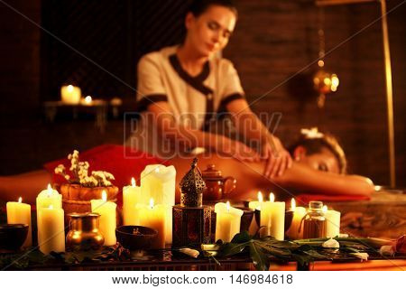 Young woman lying on wooden spa bed. Massage in spa salon with masseuse . Girl on candles background in massage spa salon.