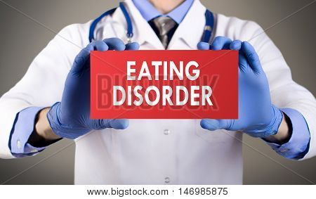 Doctor's hands in blue gloves shows the word eating disorders. Medical concept.