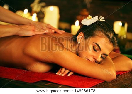 Young woman lying on wooden spa bed. Massage in spa salon. Girl on candles background in massage spa salon. In the picture visible hand masseuse.
