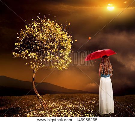 Lonely girl with umbrella near autumn tree with dark cloud sky. Sun shines through clouds on lonely girl with umbrella.