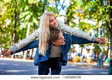 Young couple in love hugging and flirting in park and looking away. youths in love fooling around in park.