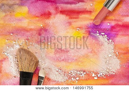 Makeup brushes and lipstick on a vibrant yellow and purple background with traces of powder and blush. Horizontal template for makeup artist's business card or flyer design with plenty of copyspace