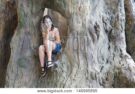 Small girl full-length portrait with funny face art painting. Female child sit in big old tree with blue butterfly drawing on her face. Children event, birthday party and creative entertainment.