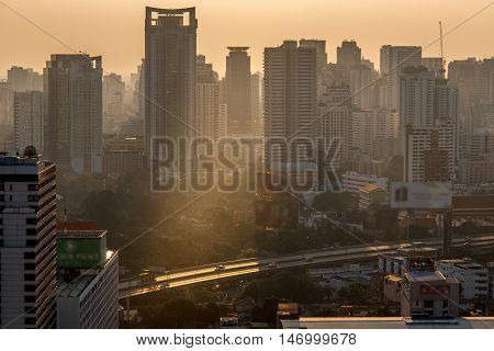 Colorful summer morning with golden light and fog between building Bangkok Thailand