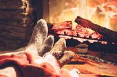 Cold fall or winter evening. People resting by the fire with blanket and tea. Closeup photo of feet  poster