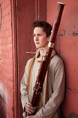 stock photo of sherwani  - Young Caucasian man outside holds a bassoon - JPG