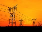 stock photo of electricity pylon  - Electricity pylons and power lines at orange sunset - JPG