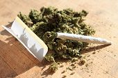 pic of marijuana cigarette  - Green cannibis with rolling paper and joint on a wooden background and natural lighting - JPG