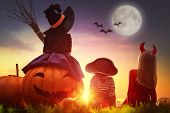 Happy brother and two sisters on Halloween. Funny kids in carnival costumes outdoors. Cheerful child poster