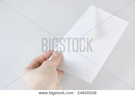 Female Hand Holding An Envelope Over White Background. Not Isolated.