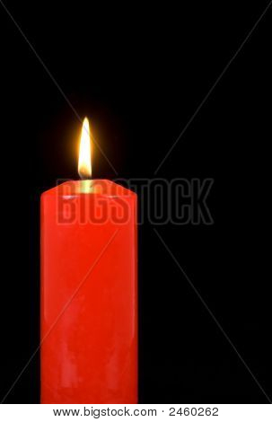 Illuminated Red Candle On Black
