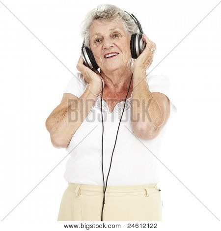 portrait of pretty senior woman listening to music with headphones over white background