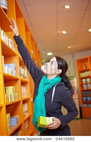 Customer Reaching For Product In Shelf